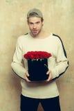 L'homme de sourire barbu tient la boîte de rose de rouge sur le mur texturisé Images libres de droits