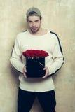 L'homme de sourire barbu tient la boîte de rose de rouge sur le mur texturisé Photographie stock libre de droits