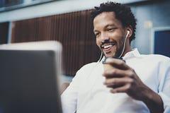 L'homme de sourire d'Afro-américain dans l'écouteur faisant l'appel visuel par l'intermédiaire du pavé tactile électronique avec  Photos stock