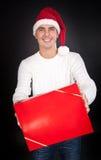 L'homme de sourire dans le chapeau de Santa donne un cadre rouge Photo libre de droits