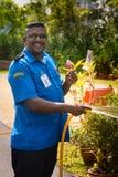 L'homme de sourire de garde de sécurité avec la glace arrose une pelouse Images stock