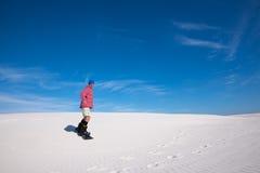 L'homme de sourire glisse vers le bas sur un surf des neiges sur la dune de sable Images stock