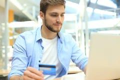 L'homme de sourire s'asseyant dans le bureau et paye par la carte de crédit avec son ordinateur portable photographie stock