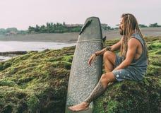 L'homme de surfer avec des dreadlocks, tatouages s'approchent de l'océan photographie stock