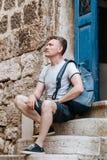 L'homme de touristes élégant s'est habillé dans une chemise blanche et des shorts avec le sac à dos au-dessus de son épaule Se re Photographie stock