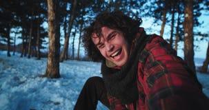 L'homme de touristes bel sur la forêt neigeuse capturant son individu devant la caméra le rendent une vidéo très enthousiaste banque de vidéos