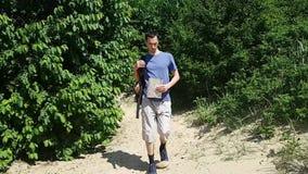 L'homme de touristes fatigué de voyageur sort lentement de la forêt sur le sable, regards à la carte et va au côté clips vidéos