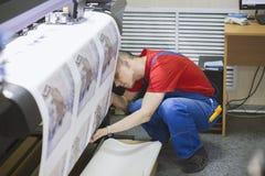 L'homme de travailleur dans l'uniforme insère le papier dans la presse typographique photographie stock libre de droits