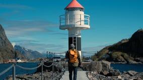 L'homme de voyage avec un sac à dos jaune va sur un terrain accidenté pittoresque au phare près de l'océan clips vidéos