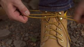 L'homme de voyageur remet le lacement vers le haut des chaussures de trekking clips vidéos