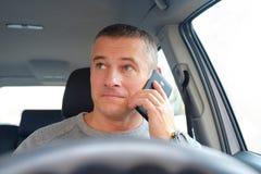 L'homme derrière la roue se reposant dans la voiture Prend un appel téléphonique photos libres de droits