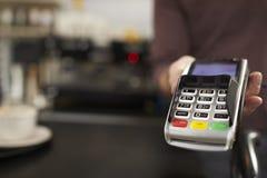 L'homme derrière le lecteur de carte de crédit de contre- offres de café, se ferment  Photo libre de droits
