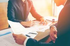 L'homme des affaires deux discutent ou réunion au sujet de papier de rapport d'investissement sur la table en bois Photographie stock