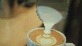 L'homme dessinant le lait au-dessus du café clips vidéos