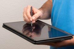 L'homme dessine sur un écran d'ordinateur portable de comprimé Photo libre de droits