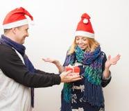 L'homme donne à la fille un présent sur le fond blanc Photographie stock libre de droits