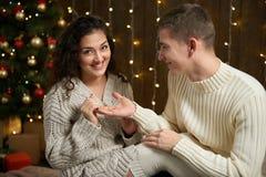 L'homme donne à la fille une bague de fiançailles, les couples dans des lumières de Noël et la décoration, habillée dans le blanc Photo libre de droits