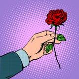 L'homme donne la fleur s'est levé Photos stock
