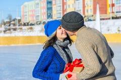L'homme donne son cadeau de surprise d'amie pour des vacances et un kisse Images libres de droits