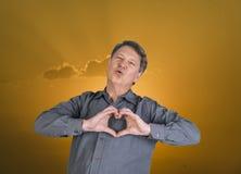L'homme donne un baiser dans le ciel et montre le signe de coeur avec des mains Photographie stock