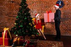 L'homme donne une fille de cadeau près de l'arbre de Noël Photos stock