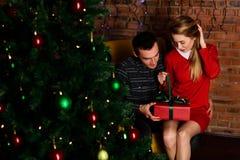 L'homme donne une fille de cadeau près de l'arbre de Noël Photographie stock