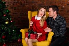 L'homme donne une fille de cadeau près de l'arbre de Noël Photo libre de droits