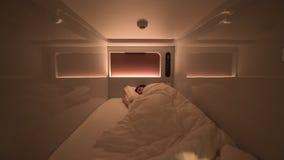 L'homme dort à l'intérieur d'une chambre d'hôtel moderne propre de capsule avec les lumières et l'aircon banque de vidéos