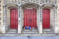 L'homme dort devant la porte d'église sur la 7ème avenue à New York City Photos libres de droits