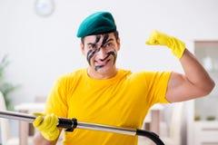 L'homme drôle dans le style militaire nettoyant la maison Photographie stock