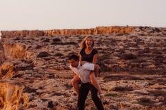 L'homme effectuent la femme de retour le soir sur la roche Photos stock