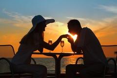 L'homme embrasse la main à la femme sur le coucher du soleil à l'extérieur Image stock