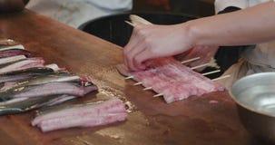 L'homme embroche les filets butterflied d'anguille avec des bâtons banque de vidéos