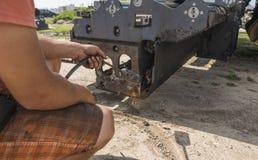 L'homme emploie un feu d'un cylindre de gaz afin de fondre le vieil asphalte sec sur une machine de machine à paver d'asphalte pe photographie stock