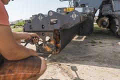L'homme emploie un feu d'un cylindre de gaz afin de fondre le vieil asphalte sec sur une machine de machine à paver d'asphalte pe photo stock