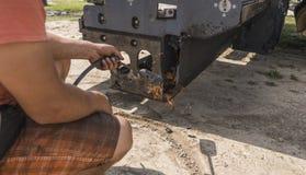 L'homme emploie un feu d'un cylindre de gaz afin de fondre le vieil asphalte sec sur une machine de machine à paver d'asphalte pe photographie stock libre de droits