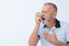 L'homme employant l'asthme inhalent image stock