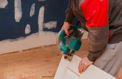 l'homme employant une circulaire a vu pour couper la r?novation de construction de porte et ? la maison du bois, outil de r?parat photographie stock libre de droits