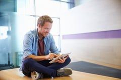 L'homme en passant habillé repose à jambes croisé utilisant la tablette Photographie stock libre de droits