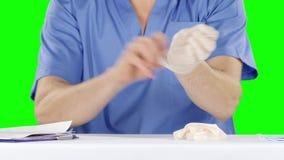 L'homme enlèvent et mettent dessus ses gants chirurgicaux Écran vert banque de vidéos