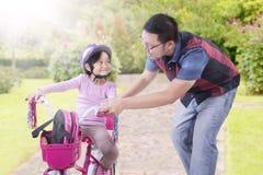 L'homme enseignent sa fille à monter la bicyclette photos libres de droits