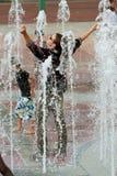 L'homme entièrement vêtu obtient la position triomphantement imbibée dans la fontaine d'Atlanta image stock