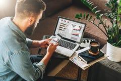 L'homme, entrepreneur, indépendant s'assied à la maison sur le divan à la table basse, utilise le smartphone, sur la table est or images libres de droits