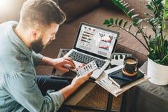 L'homme, entrepreneur, indépendant s'assied à la maison sur le divan à la table basse, utilise le smartphone, travaillant sur l'o photo libre de droits