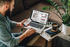 L'homme, entrepreneur, indépendant s'assied à la maison sur le divan à la table basse, utilise le smartphone, travaillant sur l'o photographie stock libre de droits