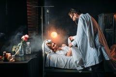 L'homme enveloppe la femme aimée par couverture dans le lit d'hôpital Photo libre de droits