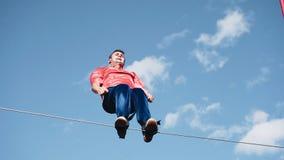 L'homme est attaché par les jambes à la corde et tourne là-dessus autour de son axe Des cascades très beaux et dangereux clips vidéos