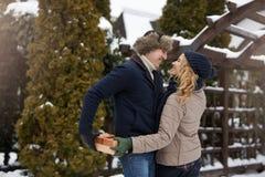 L'homme est boîte de peaux derrière le sien de retour et allant donner à sa femme un présent le jour du ` s de Valentine, le Noël Image libre de droits