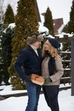 L'homme est boîte de peaux derrière le sien de retour et allant donner à sa femme un présent le jour du ` s de Valentine, le Noël Photos stock
