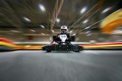 L'homme est dans le kart sur la voie karting image libre de droits